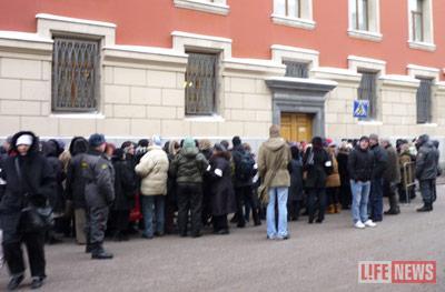Люди под присмотром милиции по одному подходят к зданию и передают свои письма