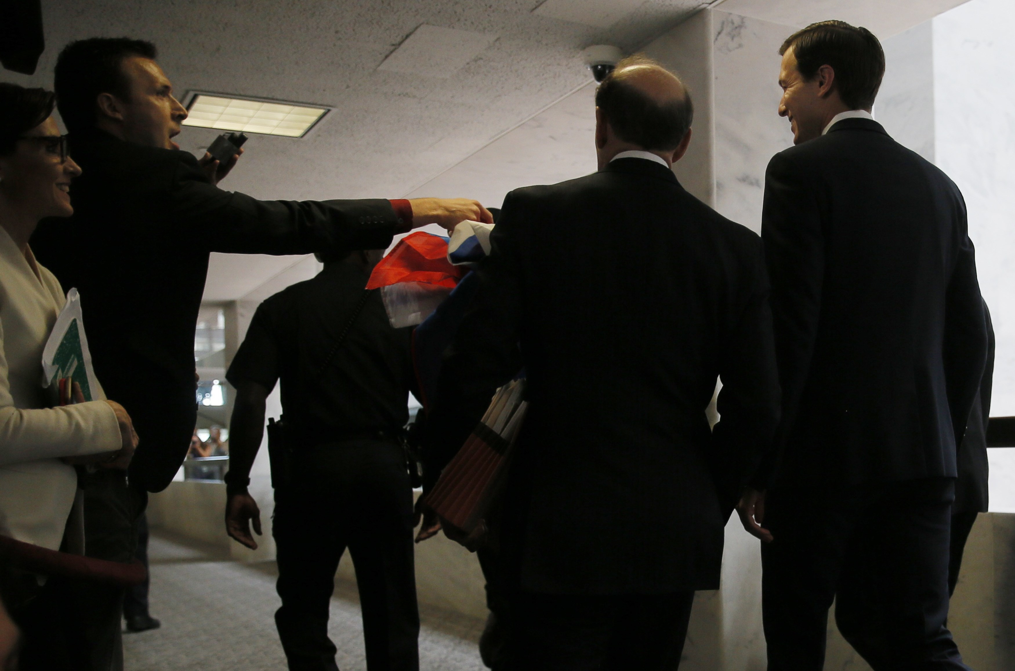 <p>Мужчина протягивает Джареду Кушнеру российский флаг с просьбой подписать его. Фото: &copy; REUTERS/Jim Bourg</p>