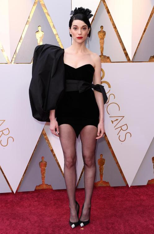 Американская 35-летняя певица St. Vincent появилась на ковровой дорожке в готическом наряде в платье с асимметрией, которое, наряду с вечерними нарядами в пол, было совсем не к месту. Фото © Rex Features / thesun.co.uk