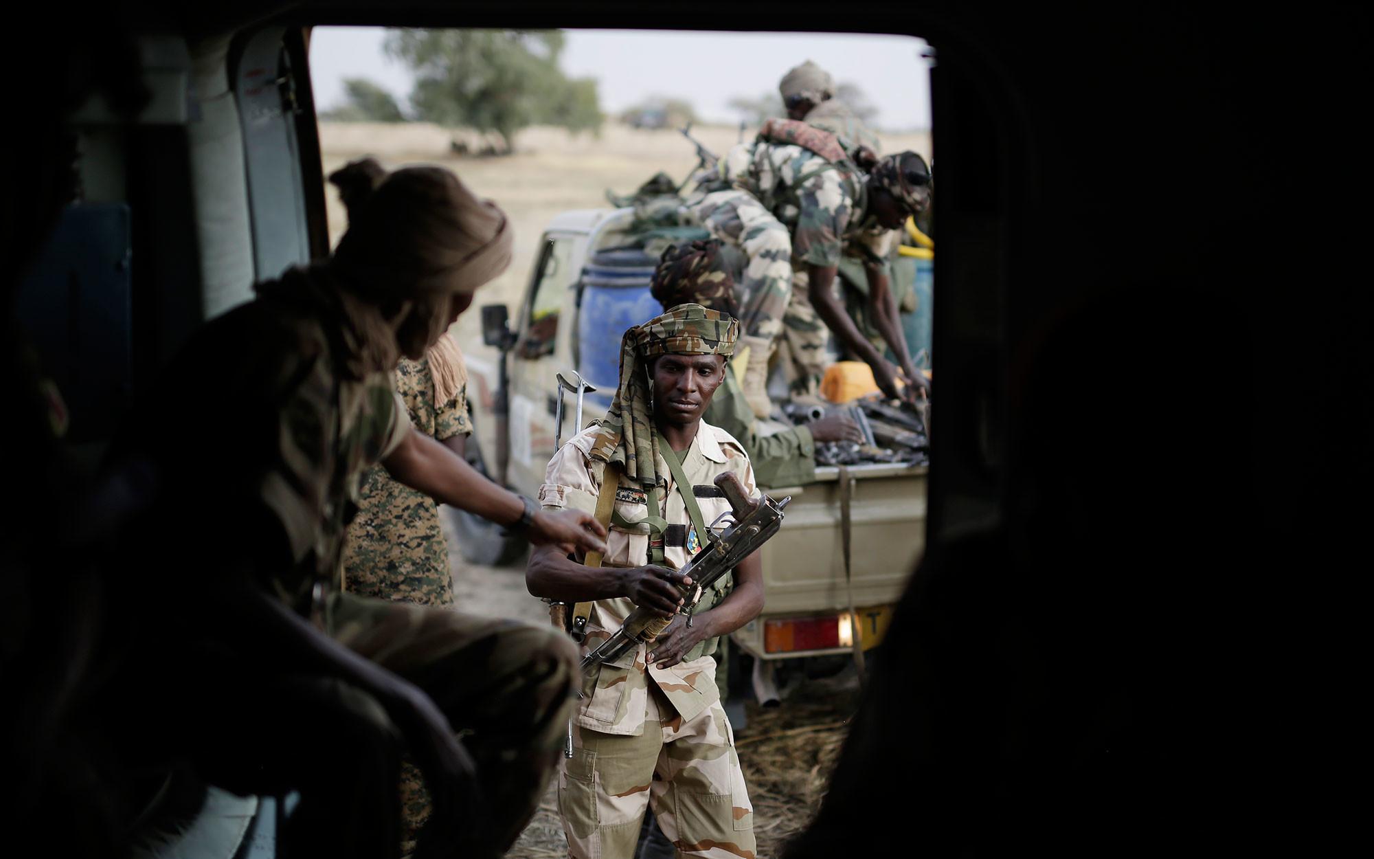 """Солдаты Чада передают оружие, захваченное у бойцов """"Боко харам"""", вертолёту в городе Дамасак, Нигерия,18 марта 2015 года. Фото: © AP Photo/Jerome Delay"""