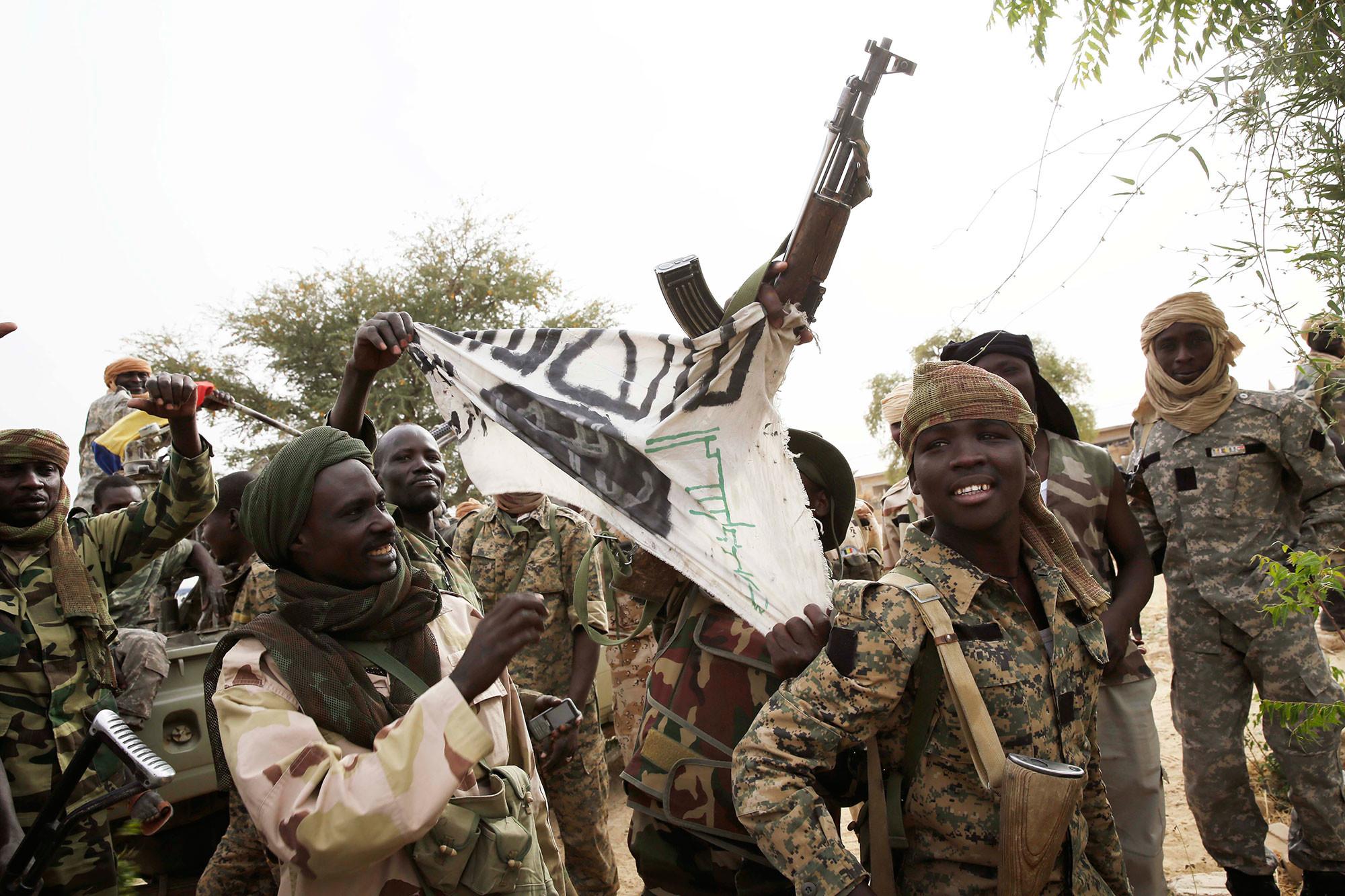 """Чадские солдаты демонстрируют флаг """"Боко харам"""" в интересах прессы в городе Дамасак, Нигерия, 18 марта 2015 года. Фото: © AP Photo/Jerome Delay"""