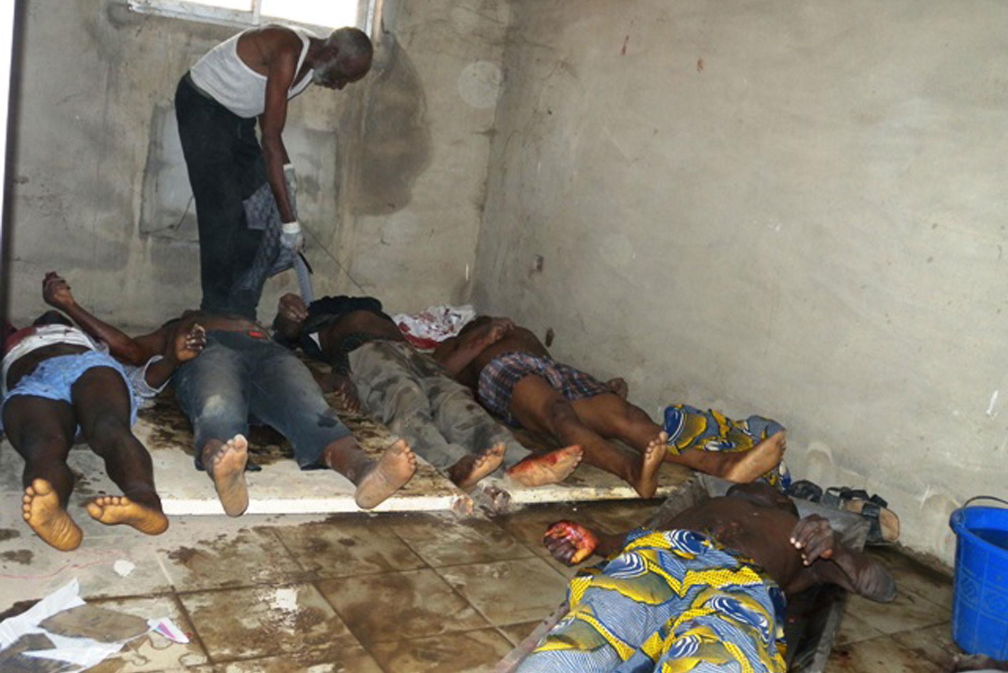 """Люди, убитые в ходе погромов, лежат на полу в больничном морге в Муби, штат Адамава на севере Нигерии, 7 января 2012 года. Нападение на ратушу, в результате которого погибло по меньшей мере 20 человек, является одним из серии смертоносных нападений, на которые претендует радикальная мусульманская секта """"Боко харам"""", обещавшая убить христиан, живущих в основном на мусульманском севере Нигерии. Фото: © AP Photo"""