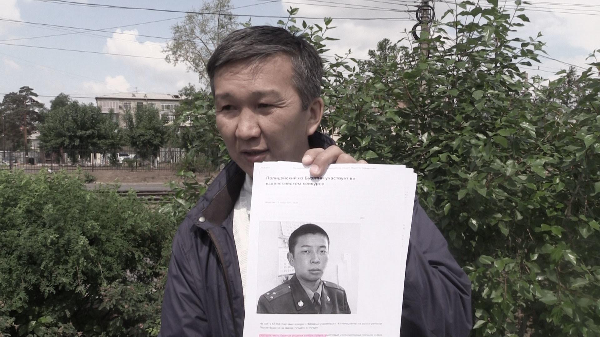 Евгений Хасоев держит фотографию участкового (лучшего в республике в 2011 году), который его избивал. Фото © L!FE