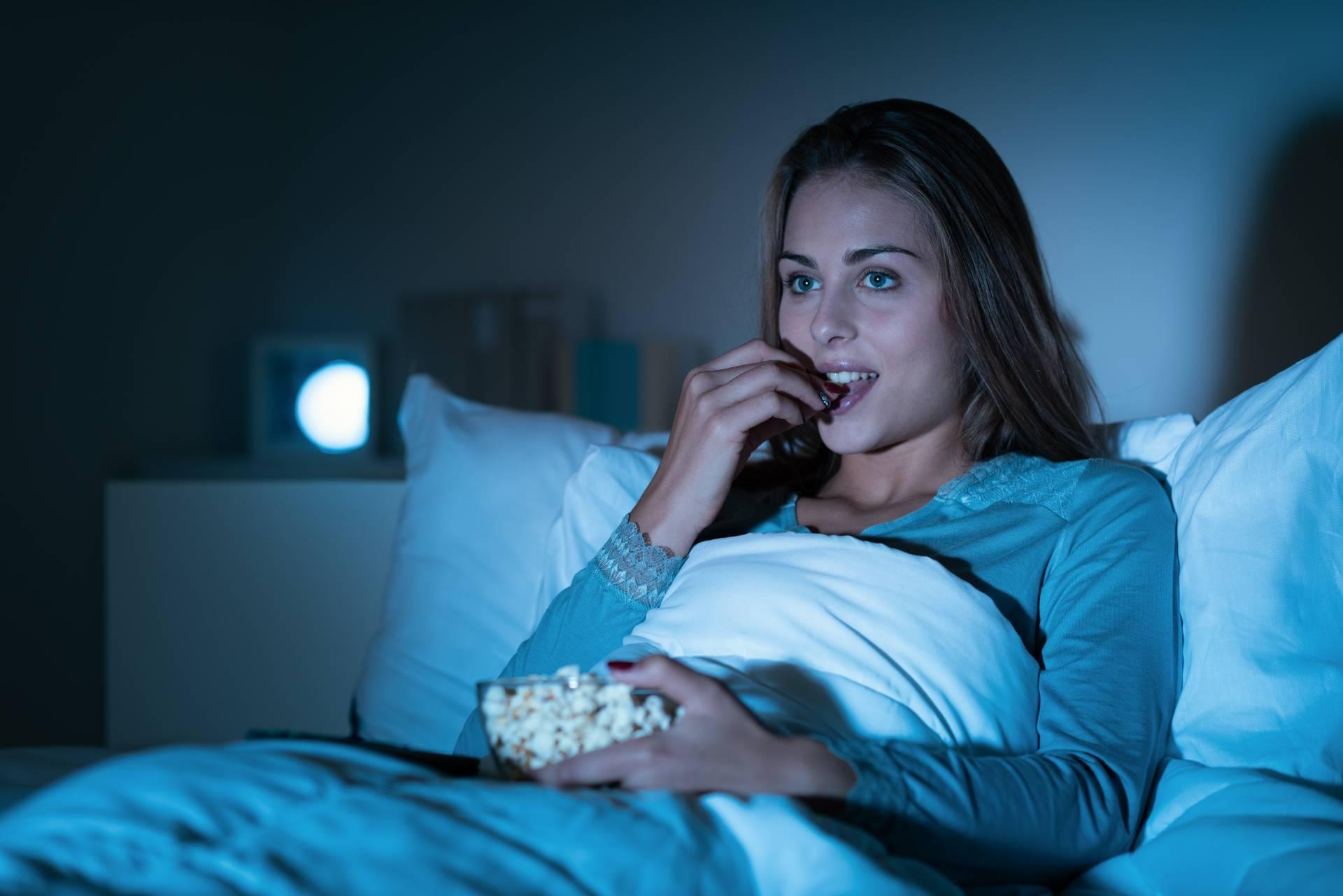 девушка ест в постели перед телевизором