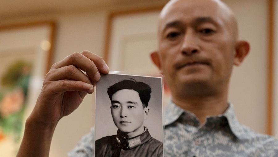 Чжан Хай держит фотографию умершего отца. Фото © ТАСС / AP Photo / Ng Han Guan