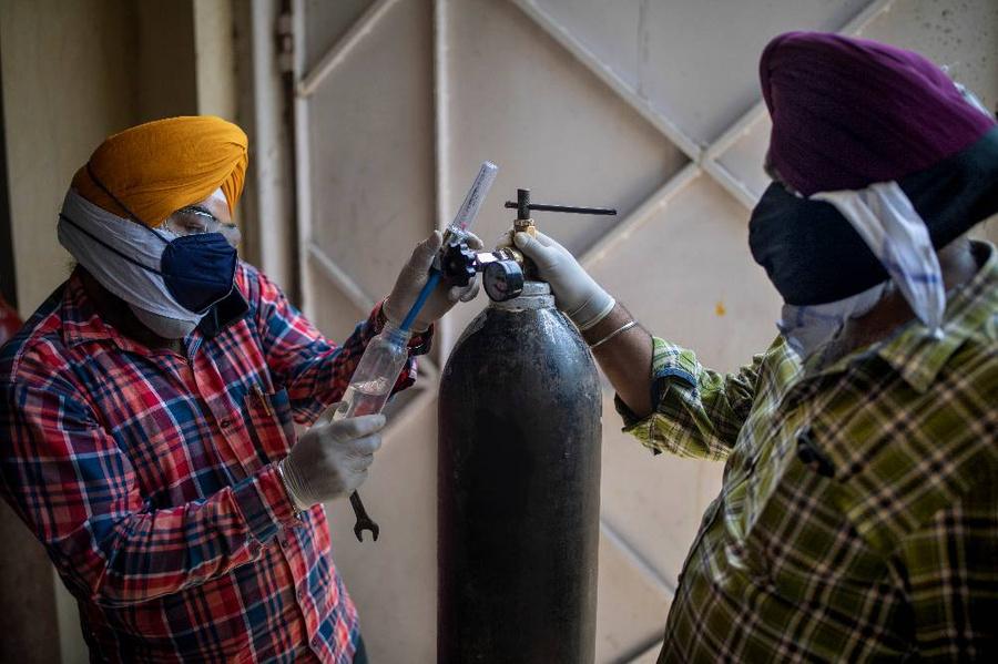 Волонтёры из храма в Нью-Дели подготавливают дозу бесплатного кислорода для очередного тяжелобольного. Фото © ТАСС / AP Photo / Altaf Qadri