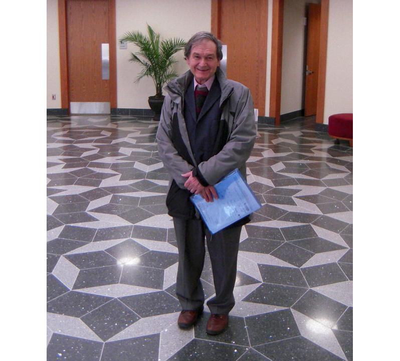 Физик Роджер Пенроуз на фоне пола, выложенного мозаикой Пенроуза. Фото © wikipedia