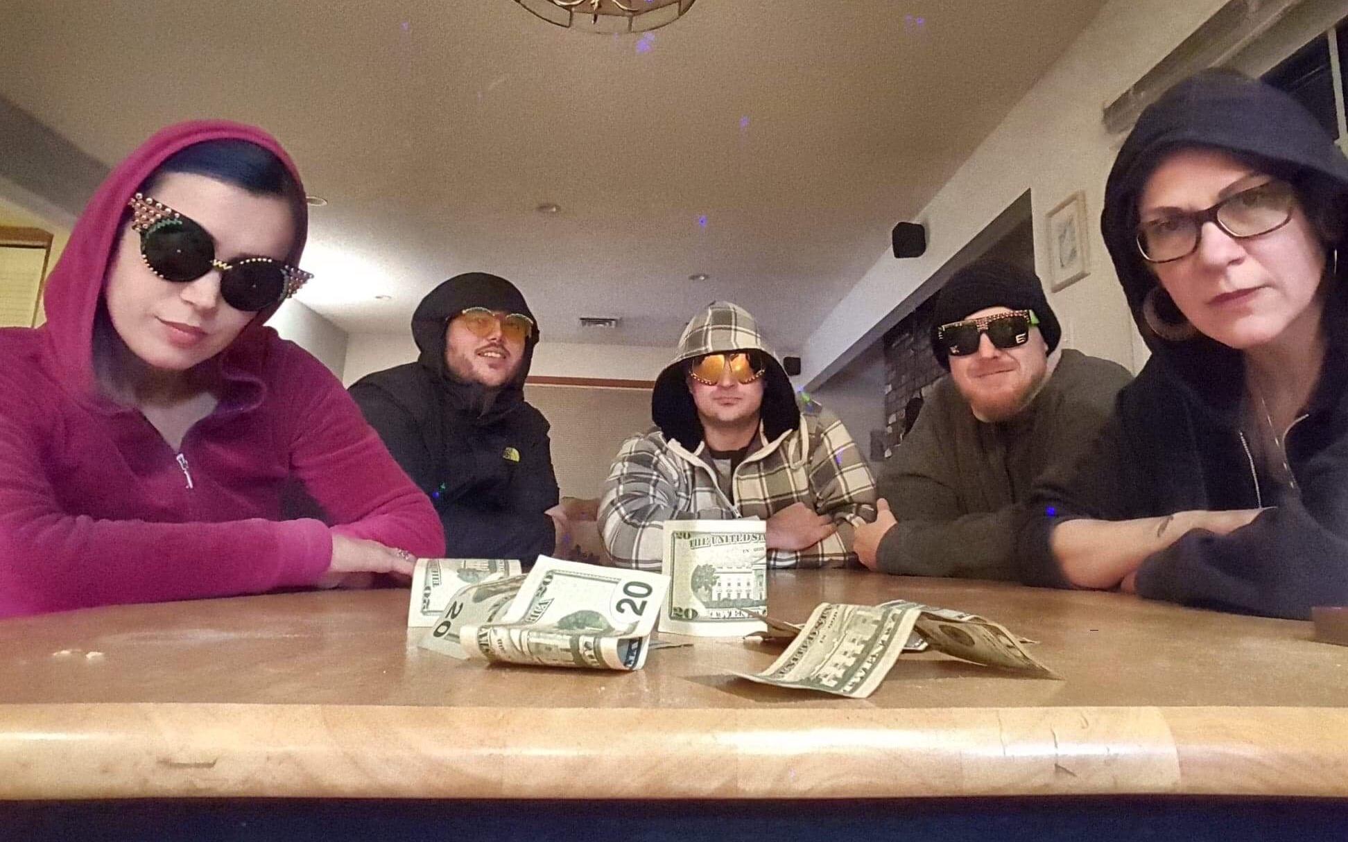 Крис в окружении друзей, на столе купюры и остатки напоминающего кокаин порошка. Фото ©facebook.com/Evans Shades
