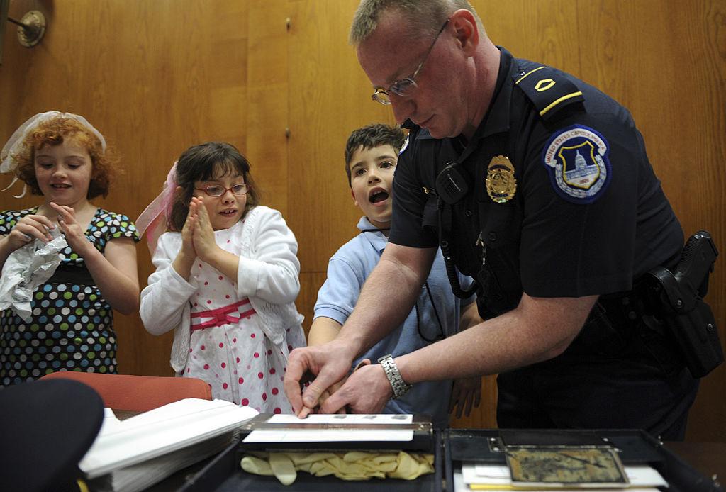 Говард Либенгуд в 2008 году берёт отпечатки у детей во время экскурсии в рамках Дня безопасности детей. Фото © Tom Williams / Roll Call / Getty Images
