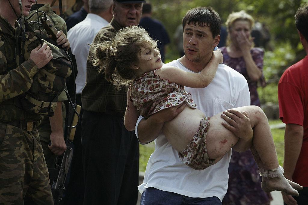 Волонтёр несёт раненую девушку после того, как спецназ штурмовал школу. Фото © Getty Images / Oleg Nikishin